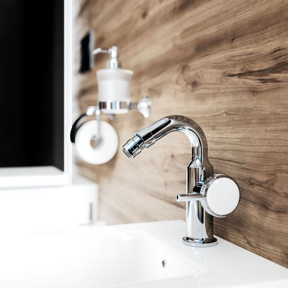 Bidet fitting in the finish chrome from the Valencia series. The lever handle is decorated with white crystal. Accessories, soap dispenser,  toilet paper roll holder in matching design in the background on the wall.